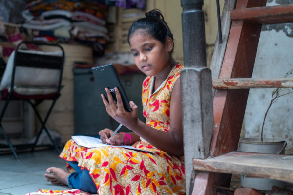 Girl taking notes as she reads from mobile phone