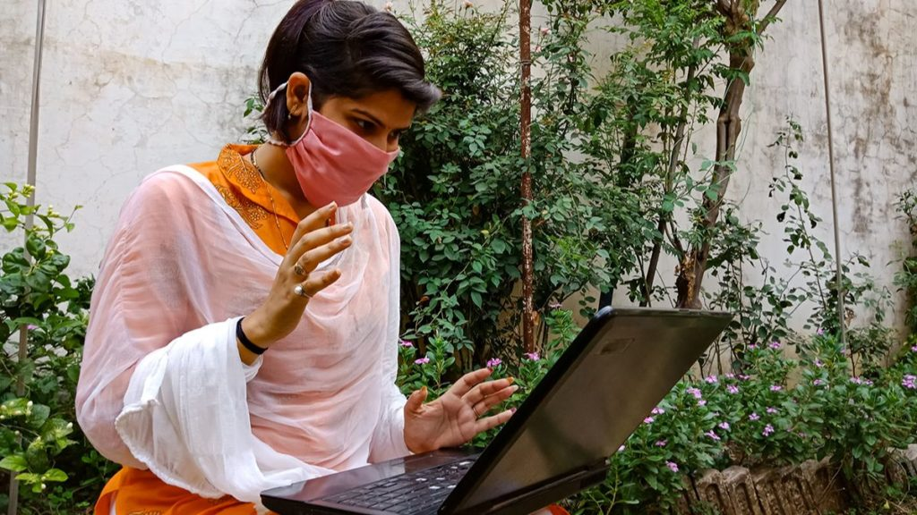 Women in face covering using a laptop